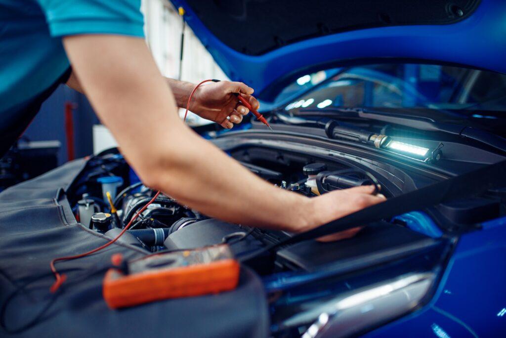 Auto electrician checks electrical circuits