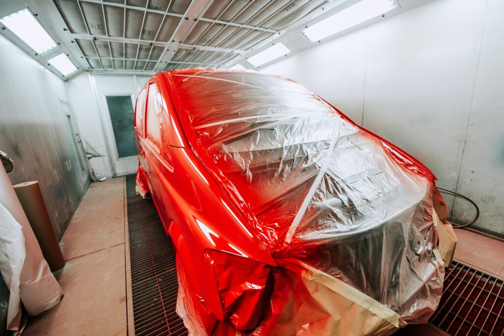 Red van being paint in special paint booth, Car painting details